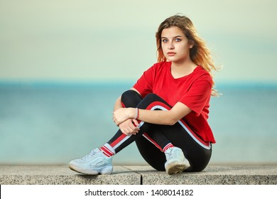 European young adult woman18-20 years old is sitting on the beach in youth clothes with sea shore on the background.