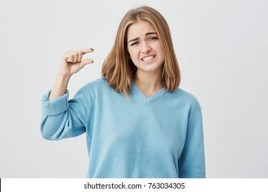 European young female wearing blue sweater with blonde hair showing something small in size with hands, gesturing, frowning brows and showing her teeth. Blonde demonstrating size of something.