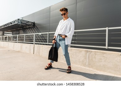 European young man hipster in stylish summer clothes in trendy sandals with a black cloth bag poses outdoors on a sunny day. Attractive guy in sunglasses in the city. Summer fashionable menswear.