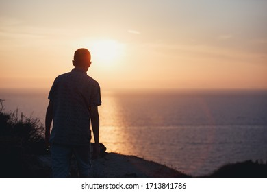 European young man looks at beautiful sunset over the Greek sea