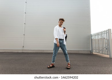 European young man in trendy white and denim clothes in  fashionable red sandals with a vintage bag walks on the city. Modern handsome guy fashion model on vacation. Summer stylish men's clothing.