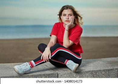 European young woman 20 years old with blond hair is sitting in casual wear on the shore with serious look,  outdoor portrait.