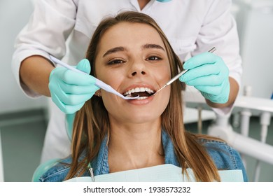 European young woman sitting in medical chair while dentist fixing her teeth at dental clinic
