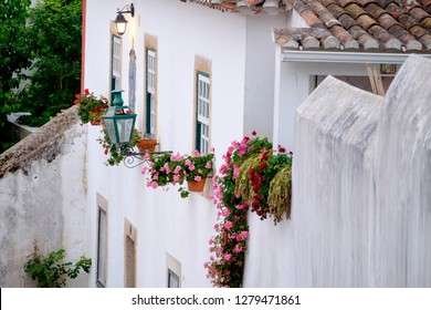 Europe,Portugal, Obidos. Ancient city wall, medieval structure encirles historic Obidos. White colored, decorated house, street latterns and potted flowers along the wall.