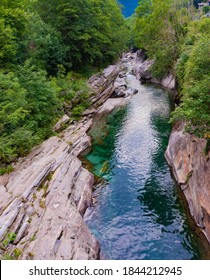 Europe.Switzerland.Crystal clear, turquoise river Verzasca.Water among stones.There are many trees on the banks.