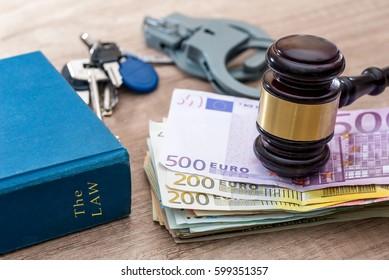 euros bills, handcuff and hammer on desk.