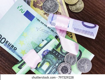 Euros of different denominations twisted into a tube