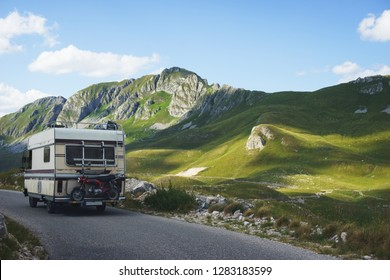 Euro-trip. Old stylish classic motorhome on the road in the mountains. Travel in the summer of Montenegro by car. National Park Durmitor.