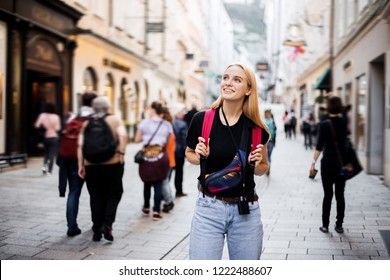 Eurotrip through the cities, travel impressions and happy mood of a happy Scandinavian woman traveler. Walk, a tourist with a backpack on his shoulders on a tour of the old town. People on travel