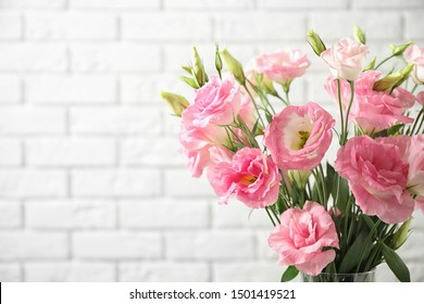 Eustoma flowers near white brick wall, space for text