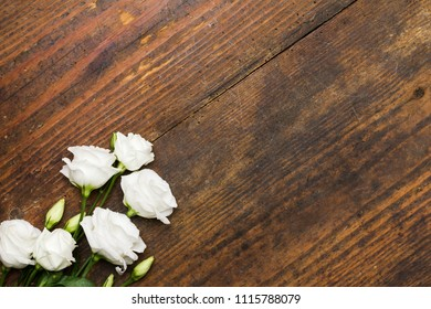 Eustoma, lisianthus flowers arranged as a beautiful natural image on aged wooden background with soft white blossoms and copy space for text