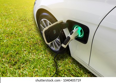 EV Car or Electric car at charging station with the power cable supply plugged in on green grass nature with sun light background. Eco-friendly alternative energy concept