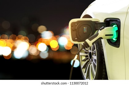 EV Car or Electric car at charging station with power supply plugged in on blurred car light on a road trip at night.