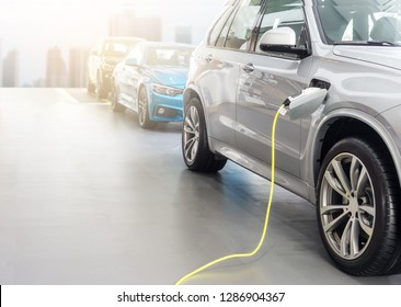 EV Car or Electric car at charging station with the power cable supply plugged in on blurred city with copy space background.Eco-friendly alternative energy concept