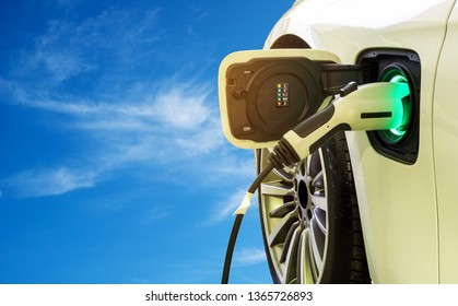EV Car or Electric car at charging station with the power cable supply plugged in on the blue sky and cloud background. Eco-friendly alternative energy concept.