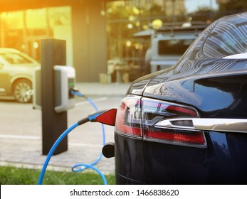 EV Car or Electric car at charging station with the power cable supply plugged in on blurred city background