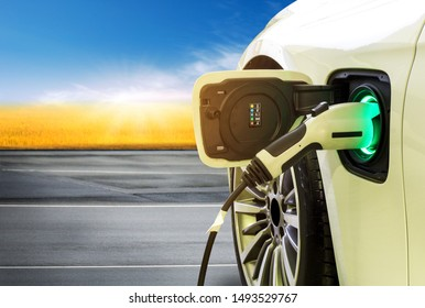 EV Car or Electric car at charging station with the power cable supply plugged in on blurred beautiful nature with soft light background. Eco-friendly alternative energy concept