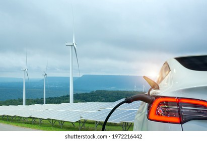 EV Car or electric power car and solar cells for electricity generation,plug of power cable electric supply during charging at ev car. - Shutterstock ID 1972216442
