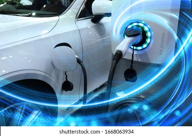EV Car or Electric vehicle at charging station with the power cable supply plugged in on blurred nature with blue enegy power effect. Eco-friendly sustainable energy concept. - Shutterstock ID 1668063934