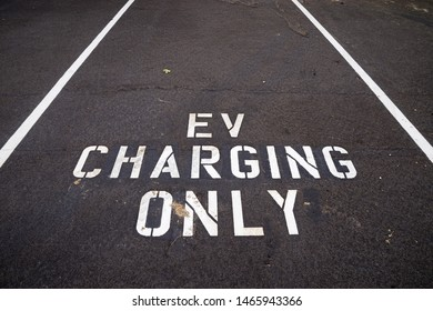 EV charging only written in white on the dark pavement of an electric vehicle charging space