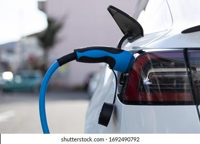 Elektroautos mit Steckdosenanschluss an einer Ladestation in der Stadt