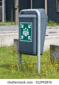 Evacuation assembly point sign on a green bin