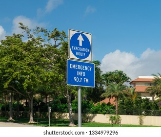 Evacuation route sign posted along highway road to direct traffic during weather disaster emergency towards safety