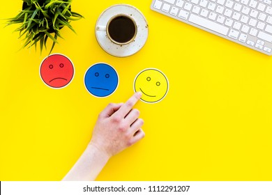 Evaluate customer service. Hand point emoji smiling, neutral, sad face on work desk on yellow background top view copy space