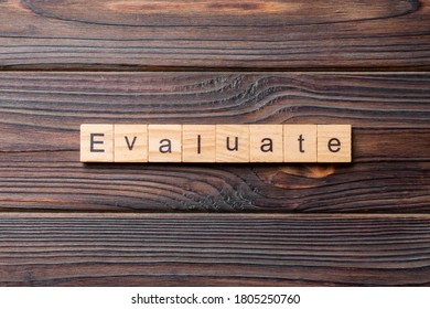 EVALUATE word written on wood block. EVALUATE text on cement table for your desing, concept.