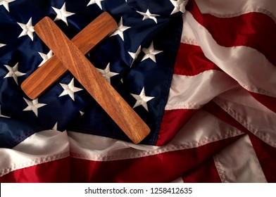Evangelical America, christianity, born again christian and fundamentalist religious right concept with close up on a wooden cross or crucifix on the american flag with dramatic light and moody tone
