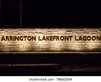 Evanston, IL - January 5th 2018: Lights shine up on the Arrington Lakefront Lagoon sign on a frigid winter night in Evanston along the Lake Michigan lakefront.