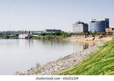 EVANSVILLE, INDIANA - APRIL 29, 2013: Scenic view of people walking near the Ohio River and the downtown Evansville business district. On the right is the Vectren building an energy holding company.