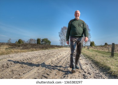 Even nature lovers are getting older. Hiking has always been a great way to experience being older with pleasure and satisfaction. In spring, an elderly man hiking in the Lüneburg Heath.