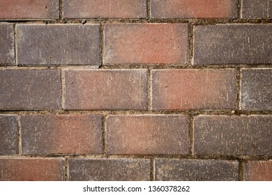 Even rows of red brown pavement tiles with scratched texture. Abstract background