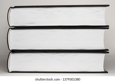 An even stack of three untitled black hardcover books that lie one upon another. Collection of volumes isolated on white paper background. Pages and binding of a closed book close up. Bottom side view
