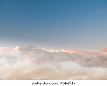 Evening above the clouds, an ocean of soft fluffy white stratocumulus clouds, moving with the wind. Rich blue sky.