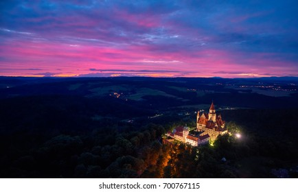 Evening, aerial view on brightly illuminated castle Bouzov on hill against red sunset in picturesque czech landscape. Fairytale, romantic Bouzov castle in late evening, Moravia, Czech republic.