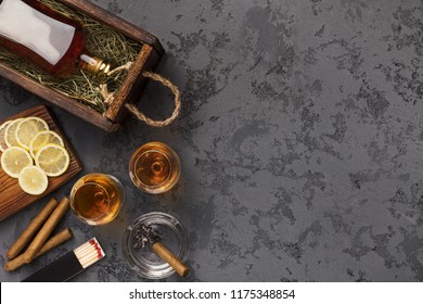 Evening alcoholic relaxation for men. Bottle and two glasses with cognac, sliced lemon and cigars on black marble table, top view, copy space