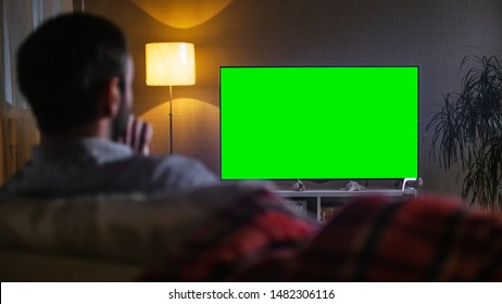 In the Evening Back View of a Middle Aged Man Sitting on a Couch Watching Big Flat Screen TV.