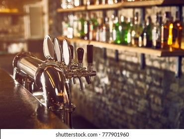 Evening at the bar. Beer taps.
