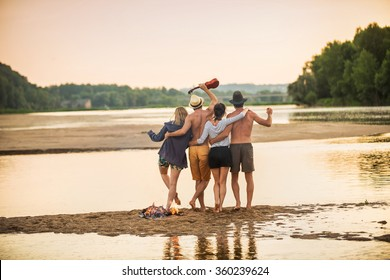 Evening at the beach Back view of four friends in their 30's are having fun around a campfire They are waving their arms to the photographer. They are looking at camera, the boys are shirtless