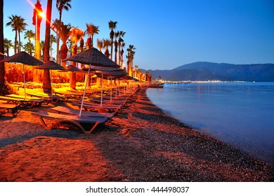 Evening beach with sun beds and umbrellas in Marmaris. Turkey