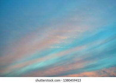 In the evening blue sky Cirrus clouds are arranged in strips diagonally. Color stripes clouds pink, orange, red. Change of weather, forecast, meteorology. Background, backdrop.