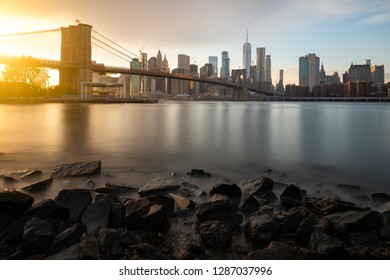 Evening by the East River in New York City. View of Brooklyn Bridge and Lower Manhattan during sunset.