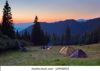 Evening by the fire in the mountains. Camping in tents in the mountains.
