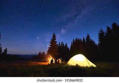 Abends Camping bei Feuer, Fichtenwald und Berge auf dem Hintergrund. Gruppe von Freunden, die sich in der Nähe von hellem Feuer ausruhen. Leute, die in der Nähe von Touristenzelt sitzen unter Nachthimmel voller Sterne und Milchstraße.