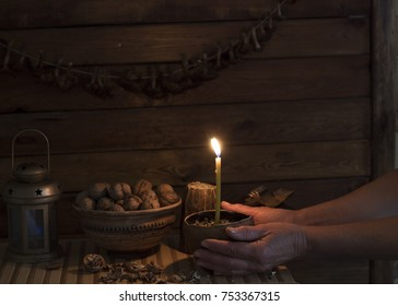 Evening. candle on the background of a wooden wall. Shelf with objects.