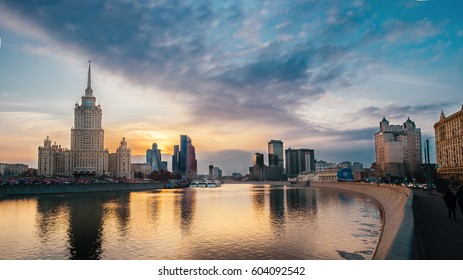 Evening city landscape with sun over Moscow river at sunset with Stalin Skyscraper reflection, Outdoor travel background, Moscow, Russia. Architecture landmark of Russia, Moscow night city panorama