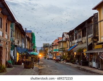 Evening in the city. Many birds fly fast in the sky at sunset. Street of Kampot Old Town. Cambodia