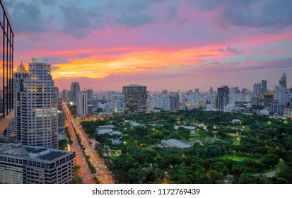 Evening cityscape at Lumpini park from roof top bar on hotel with sunset sky and clouds at Bangkok , Thailand.